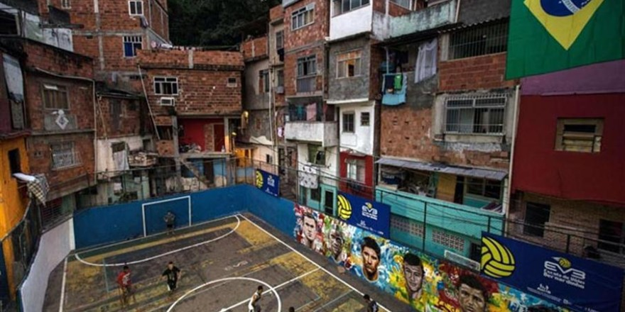 Youngsters play football at a field of Tavares Bastos shantytown (favela) in Rio de Janeiro, Brazil on June 8, 2014, just four days ahead of the FIFA World Cup 2014.  AFP PHOTO / YASUYOSHI CHIBA   FBL-WC-2014-BRAZIL-FAVELA